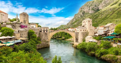 Stand on the riverbanks of the Neretva River for great views of the Stari Most Bridge and people jumping into the river
