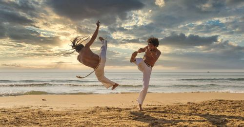 Practice the rhythmic movements of Capoeira