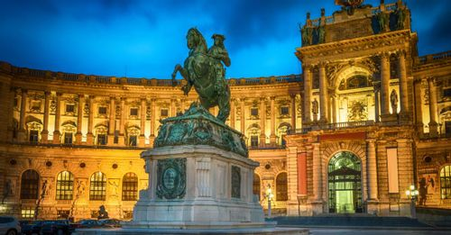 Enjoy a scenic sunset behind famous Austrian buildings from Heldenplatz